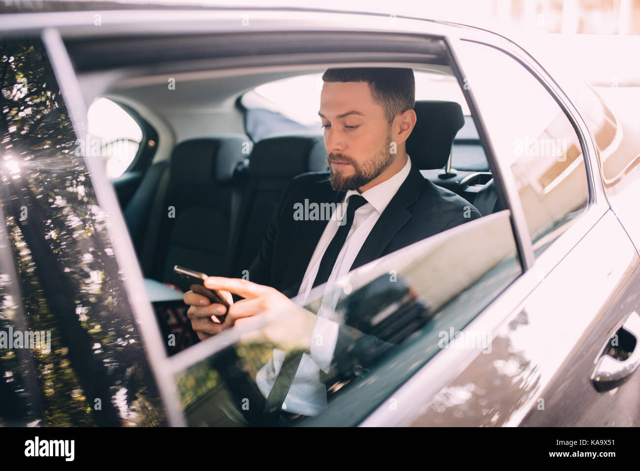 Businessman talking on the mobile phone and looking outside the window while sitting on back seat of a taxi - Stock Image