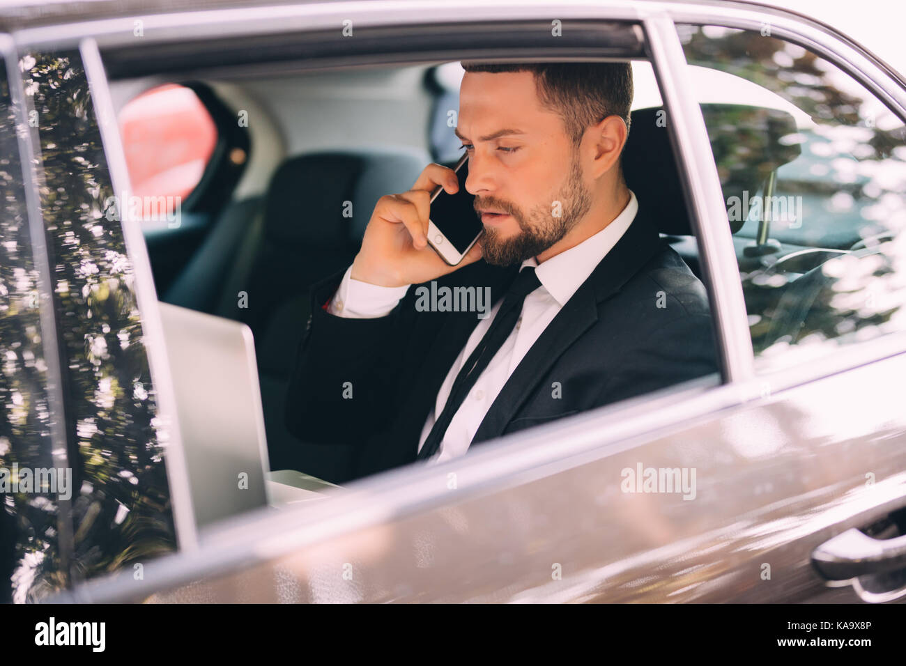 Businessman talking on the mobile phone and looking outside the window while sitting on back seat - Stock Image