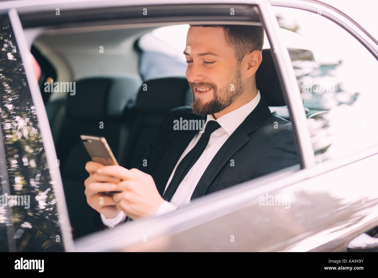 Serious businessman using his phone in his car - Stock Image