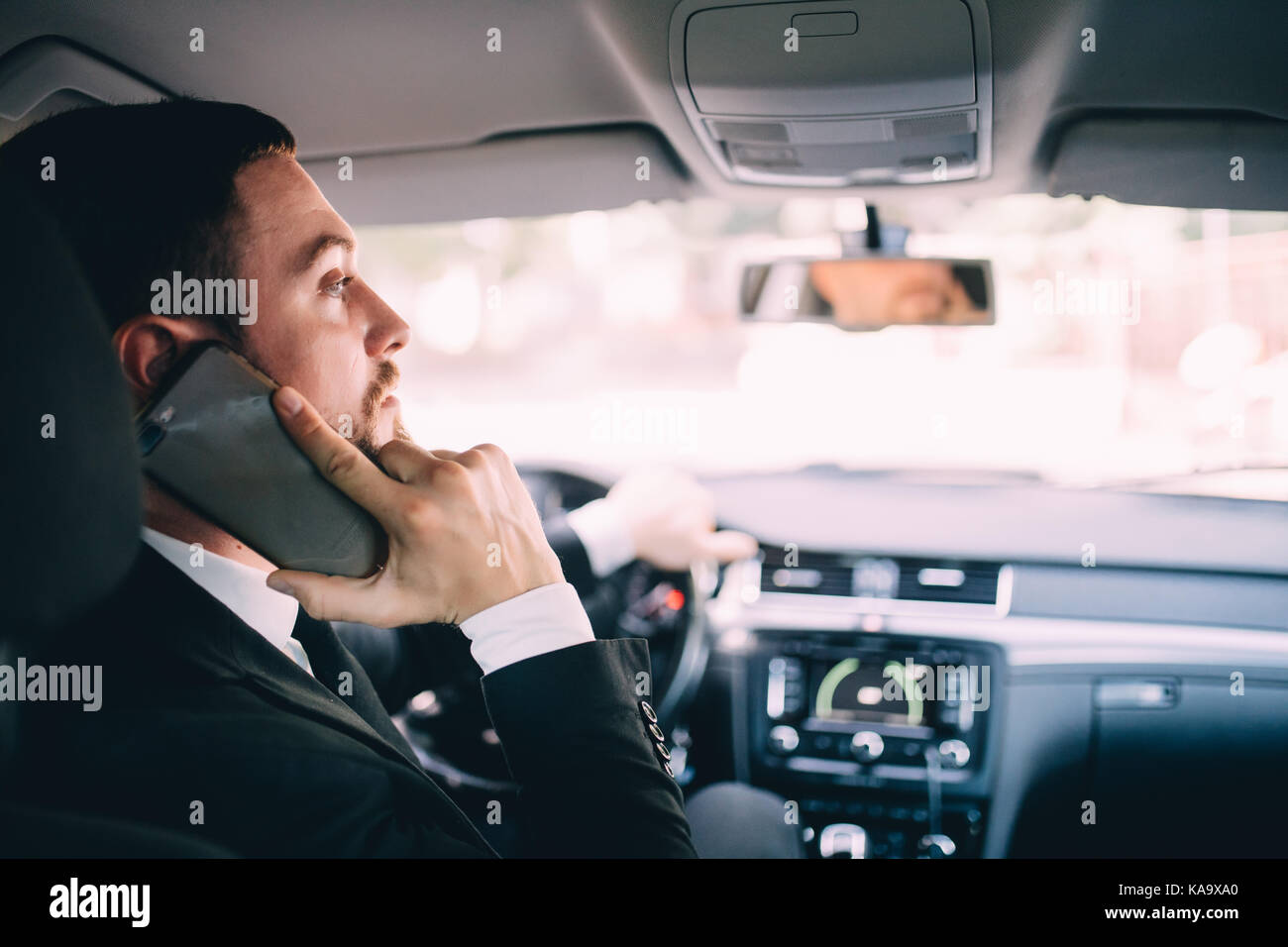Man using his phone while driving the car - Stock Image