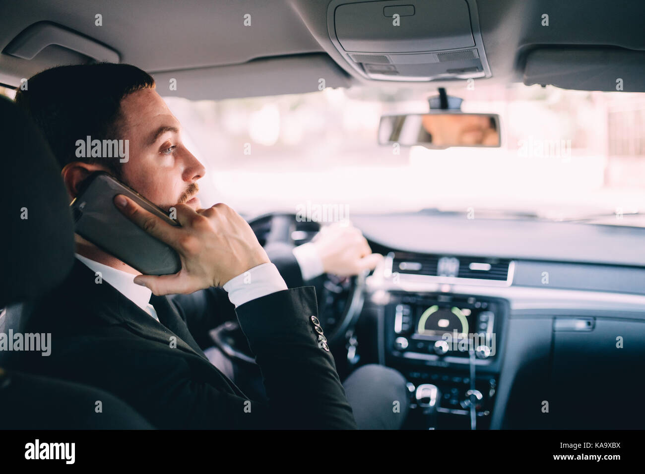 Man looking at mobile phone while driving a car. - Stock Image