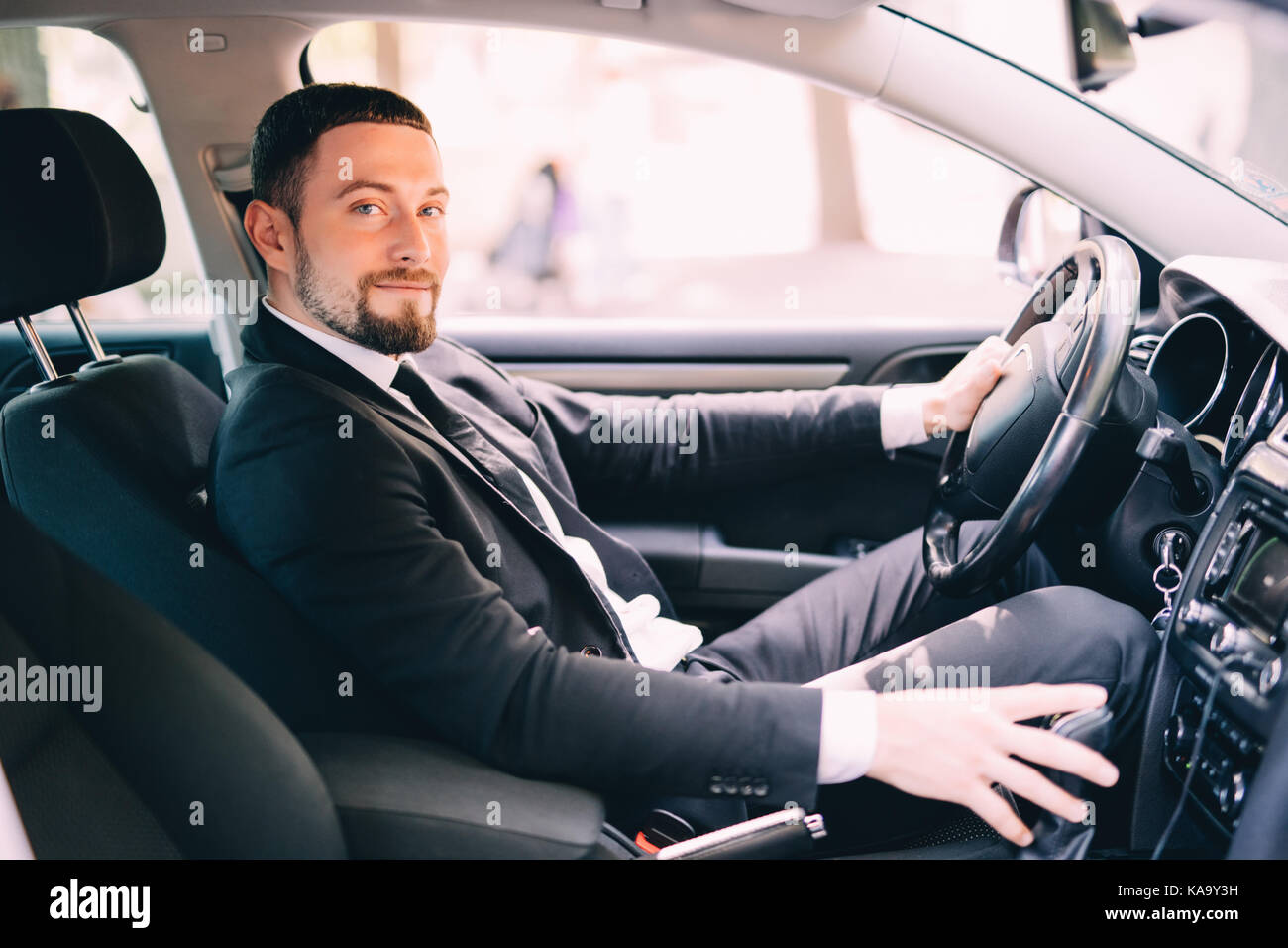 transport, business trip, speed, destination and people concept - close up of young man in suit driving car Stock Photo