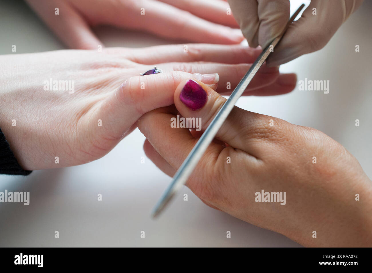 Professional manicurist manicuring clients fingernails in nail salon, close up of hands - Stock Image