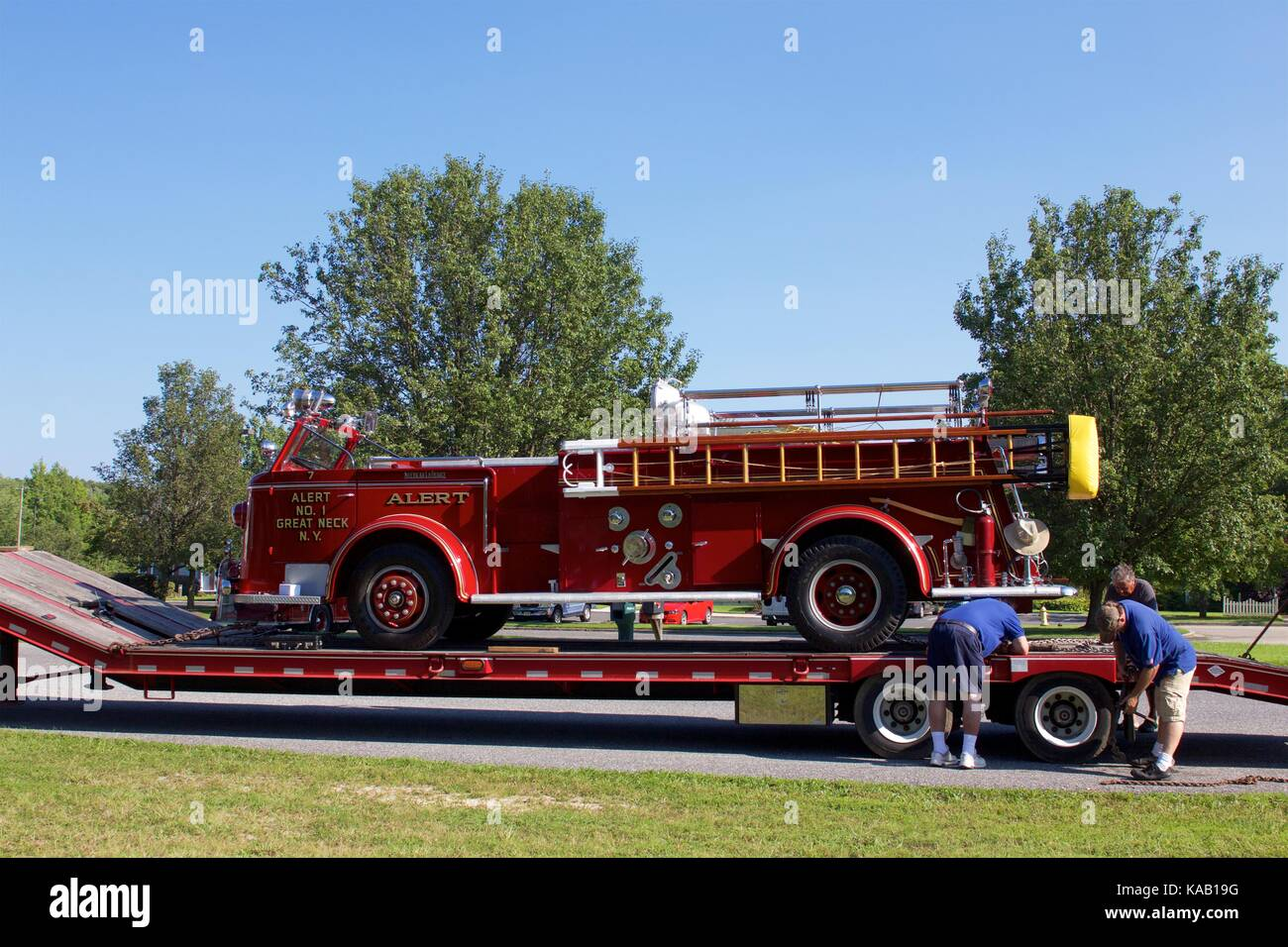 Some of the historic fire engines are transported to the muster via flatbed trailer. - Stock Image