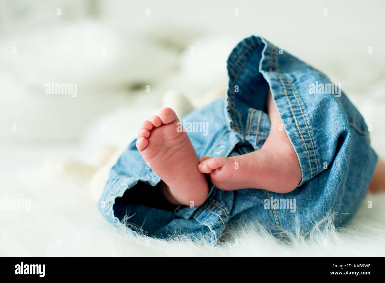 Little baby boy feet, baby lie down in bed in the afternoon, natural light - Stock Image