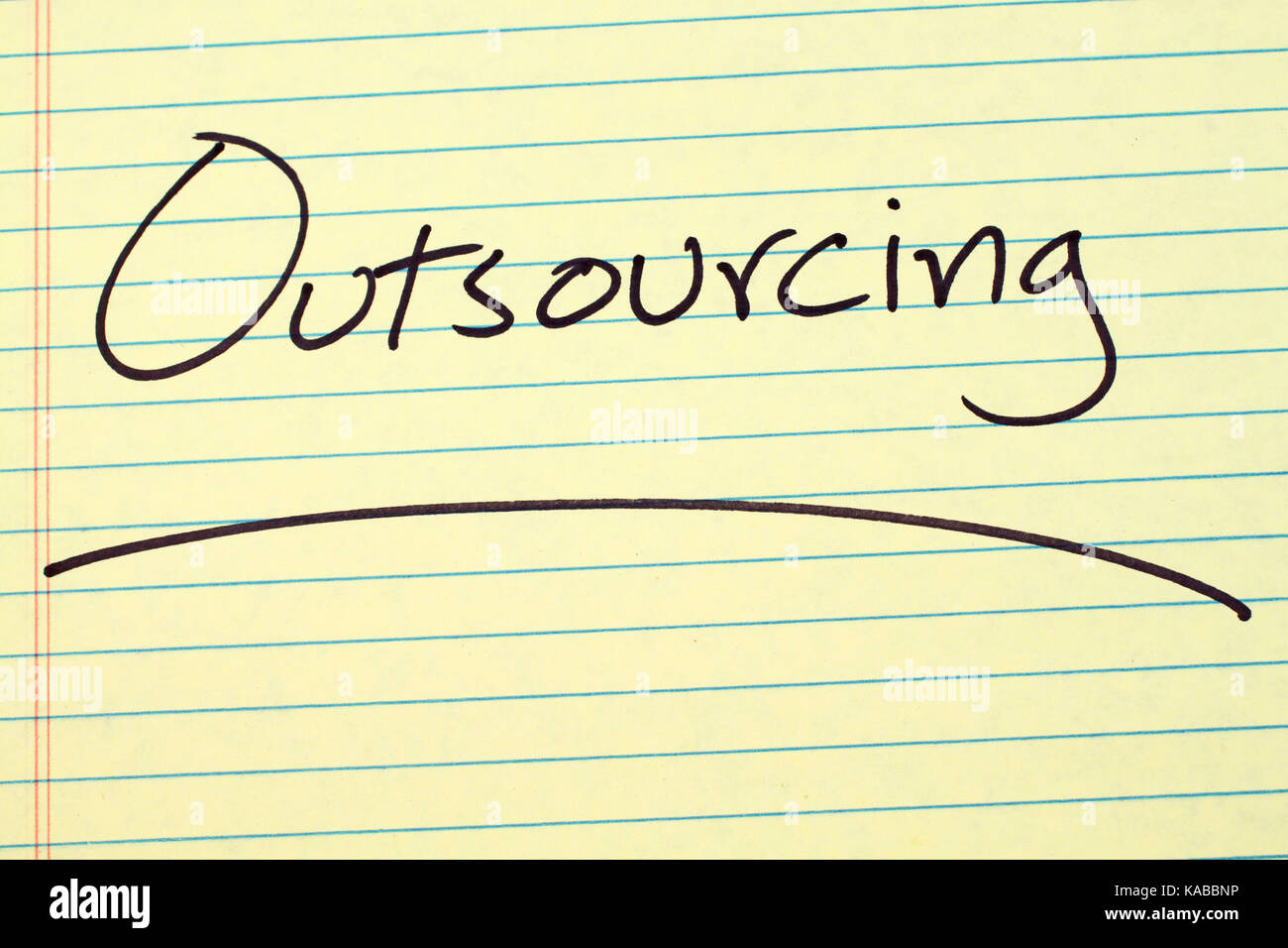 The word 'Outsourcing' underlined on a yellow legal pad - Stock Image