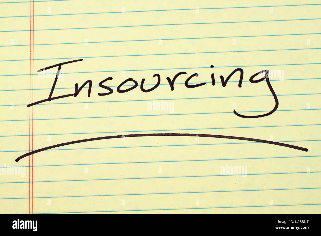 """The word """"Insourcing"""" underlined on a yellow legal pad Stock Photo"""