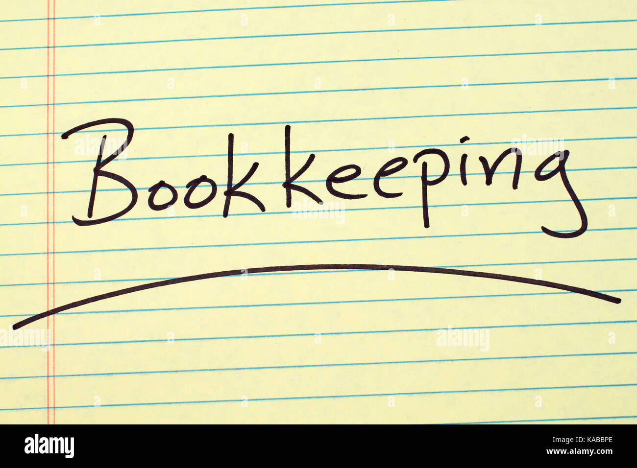 The word 'Bookkeeping' underlined on a yellow legal pad - Stock Image