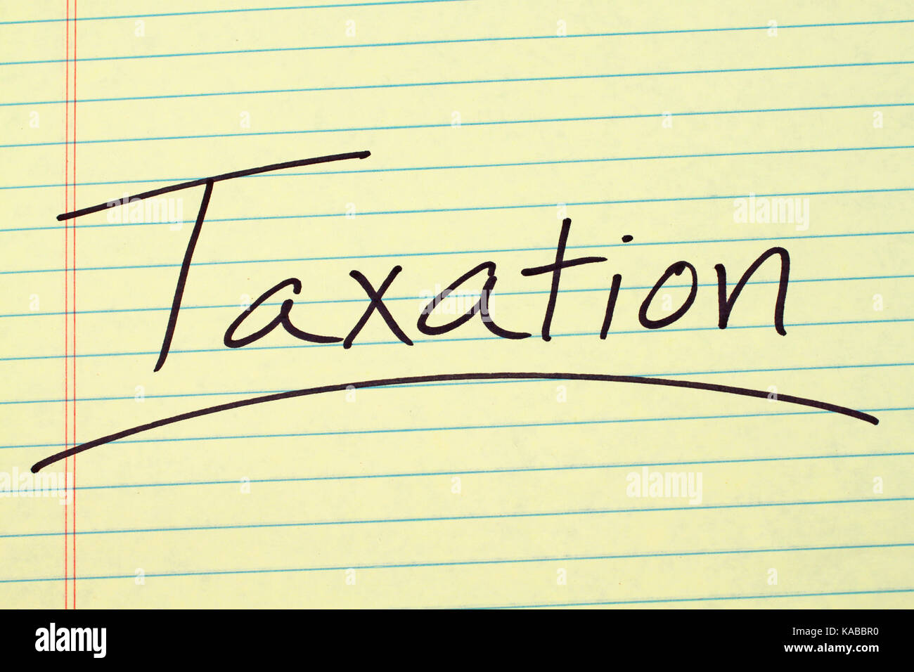The word 'Taxation' underlined on a yellow legal pad - Stock Image