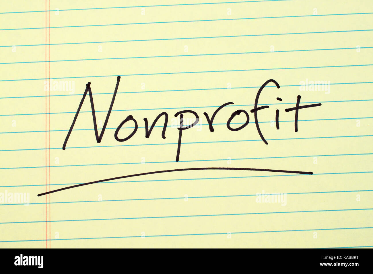 The word 'Nonprofit' underlined on a yellow legal pad - Stock Image