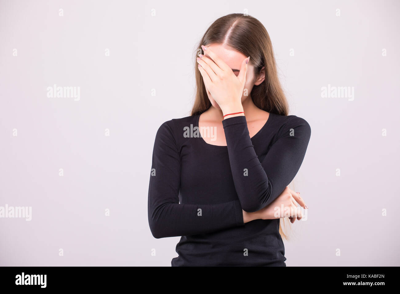 Girl with distrust and doubt looks forward, her arms near face - Stock Image