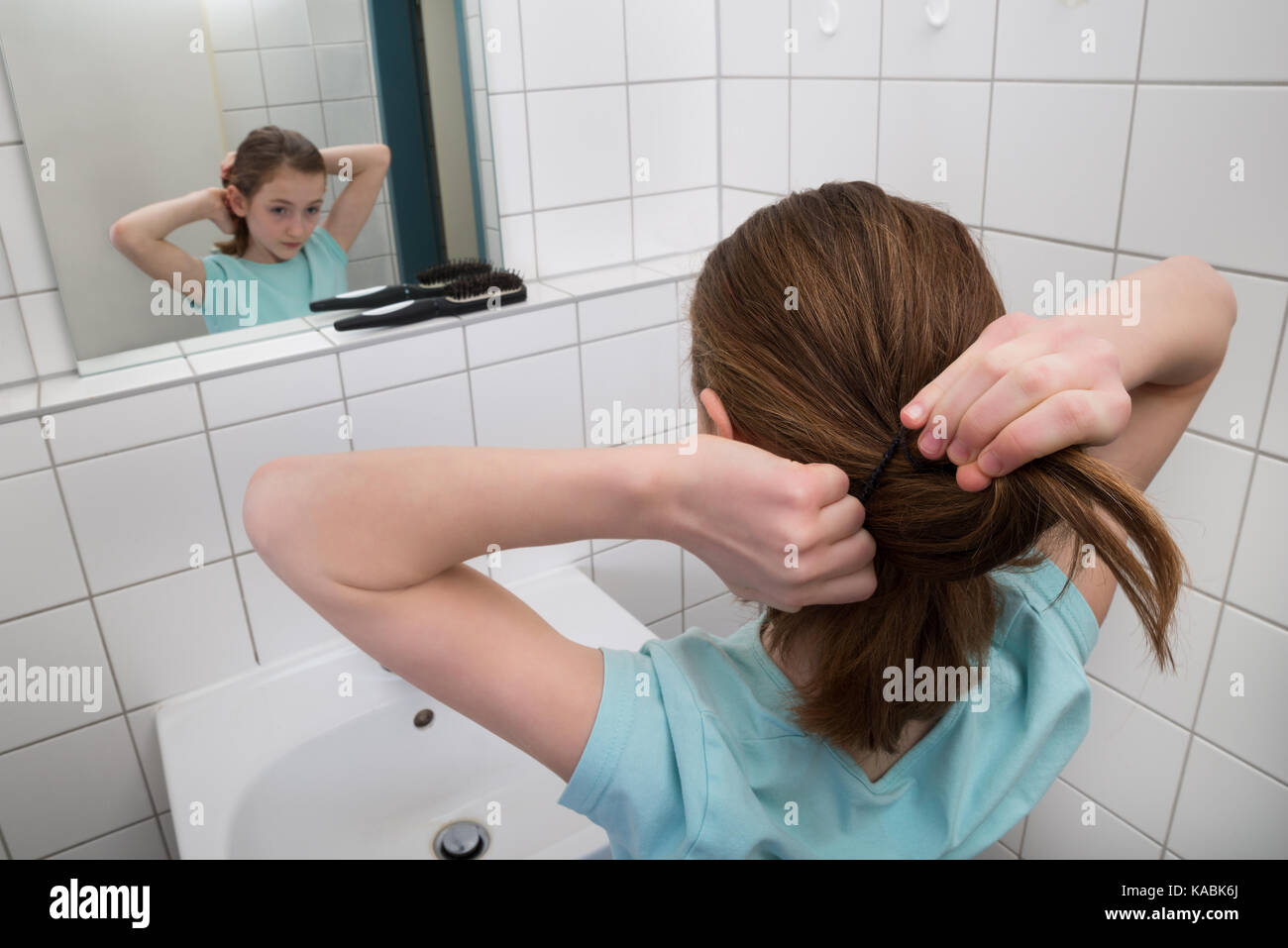 Little Girl Tying Hair In Front Of Mirror In Bathroom - Stock Image