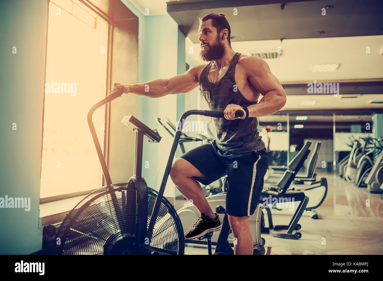 Young Man Using Exercise Bike At The Gym Fitness Male Air For Cardio Workout Crossfit