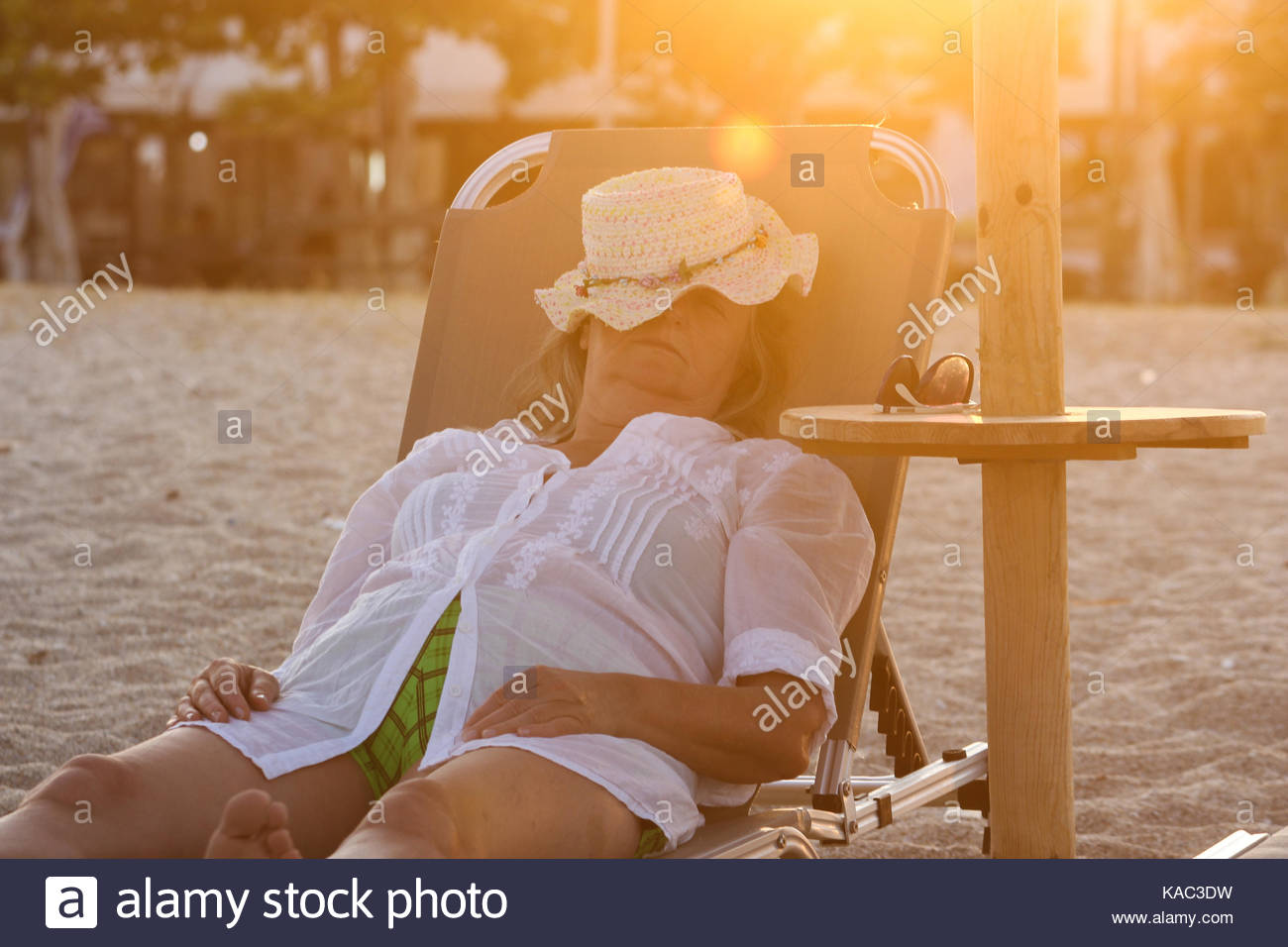 Woman Laying on the Sunbed and Sleeping on the Beach - Stock Image