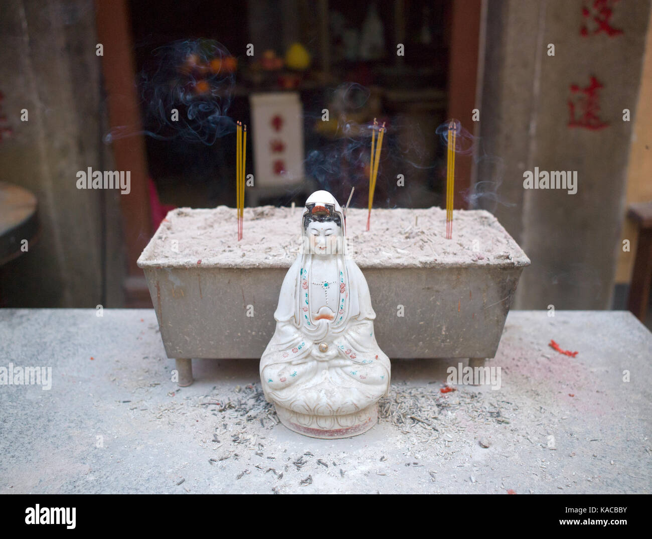 Miniature statue of female Buddhist deity sitting in front of sand-filled trough where incense sticks smoulder. - Stock Image