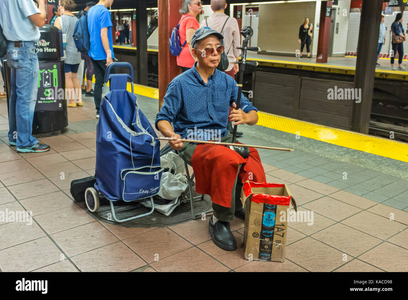 A street musician playing music in the subway in Manhattan, New York City. - Stock Image