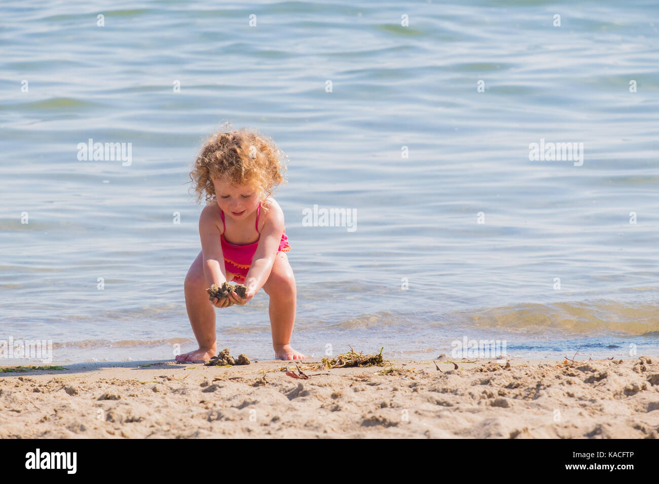 Small female child plays at and enjoys the coolwater on a rare hot day in Orillia Ontario Canada. - Stock Image