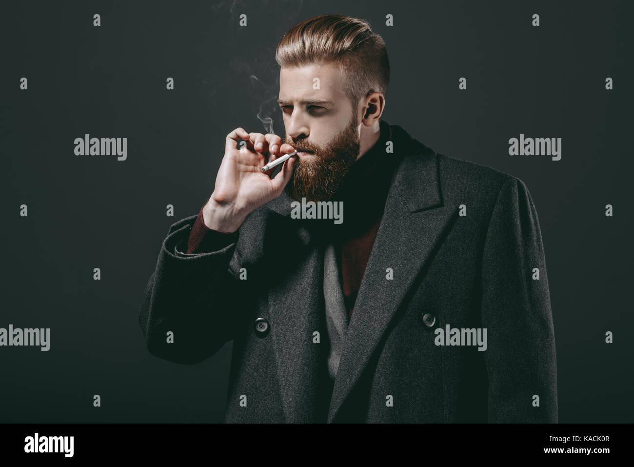 stylish man smoking cigarette - Stock Image