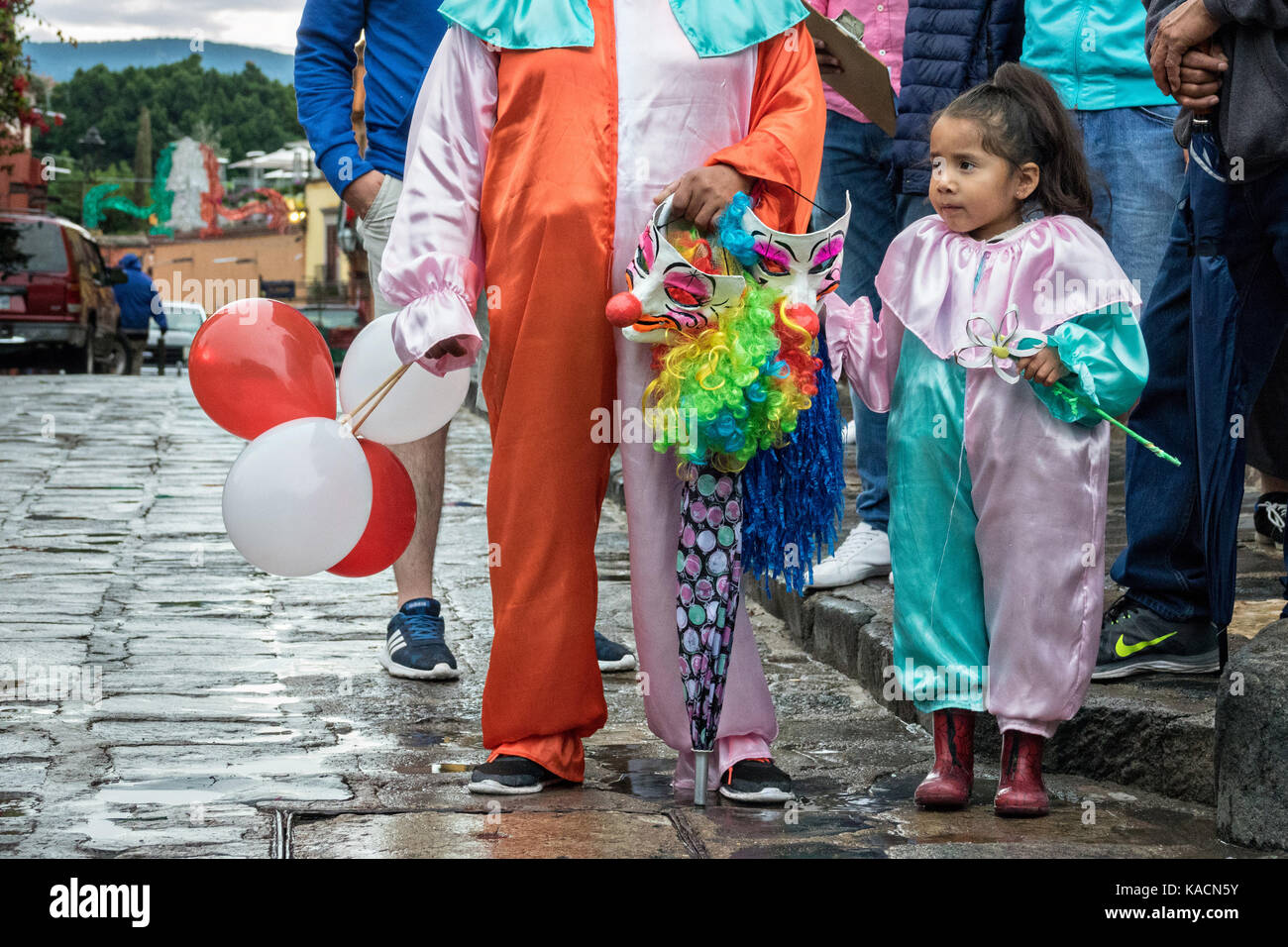 A young girl in clown costume watches a procession pass through the Jardin Allende during the week long fiesta of - Stock Image