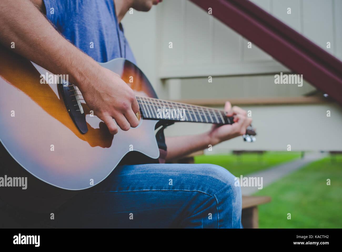 A young man plays a guitar. - Stock Image