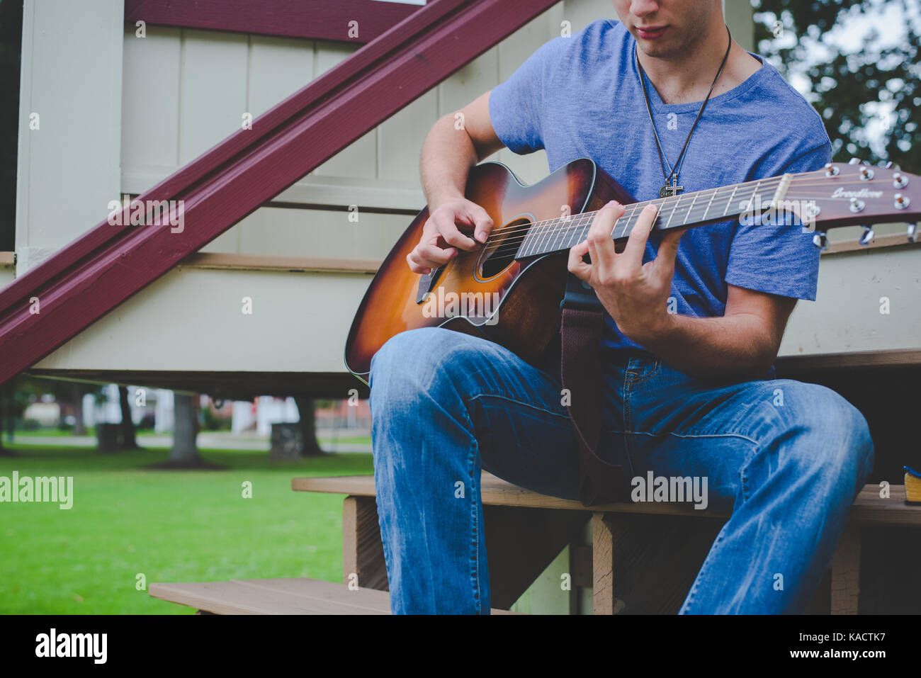 A young man plays a guitar. - Stock Image