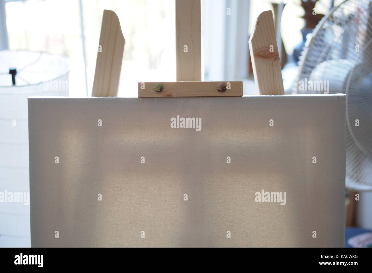 Light shining through a blank artist's canvas resting on a wooden easel. - Stock Image
