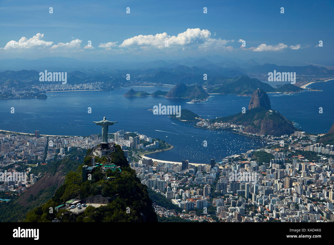 Christ the Redeemer statue atop Corcovado, and Sugarloaf Mountain, Rio de Janeiro, Brazil, South America - aerial Stock Photo