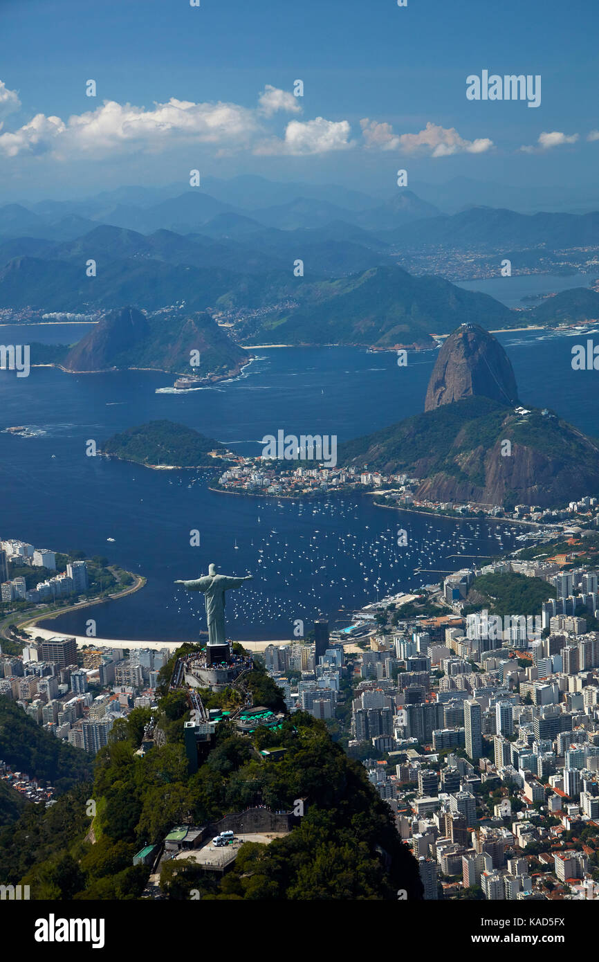 Christ the Redeemer statue atop Corcovado, and Sugarloaf Mountain, Rio de Janeiro, Brazil, South America - aerial Stock Photo