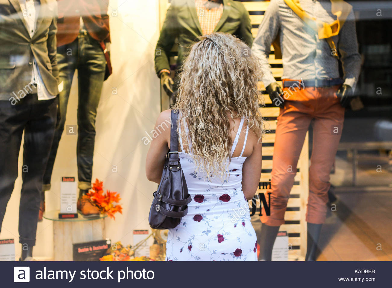 Window Shopping - Attractive Curly Blonde Girl Standing in Front of the Shop Window and Looking at Clothes. Consumerism - Stock Image
