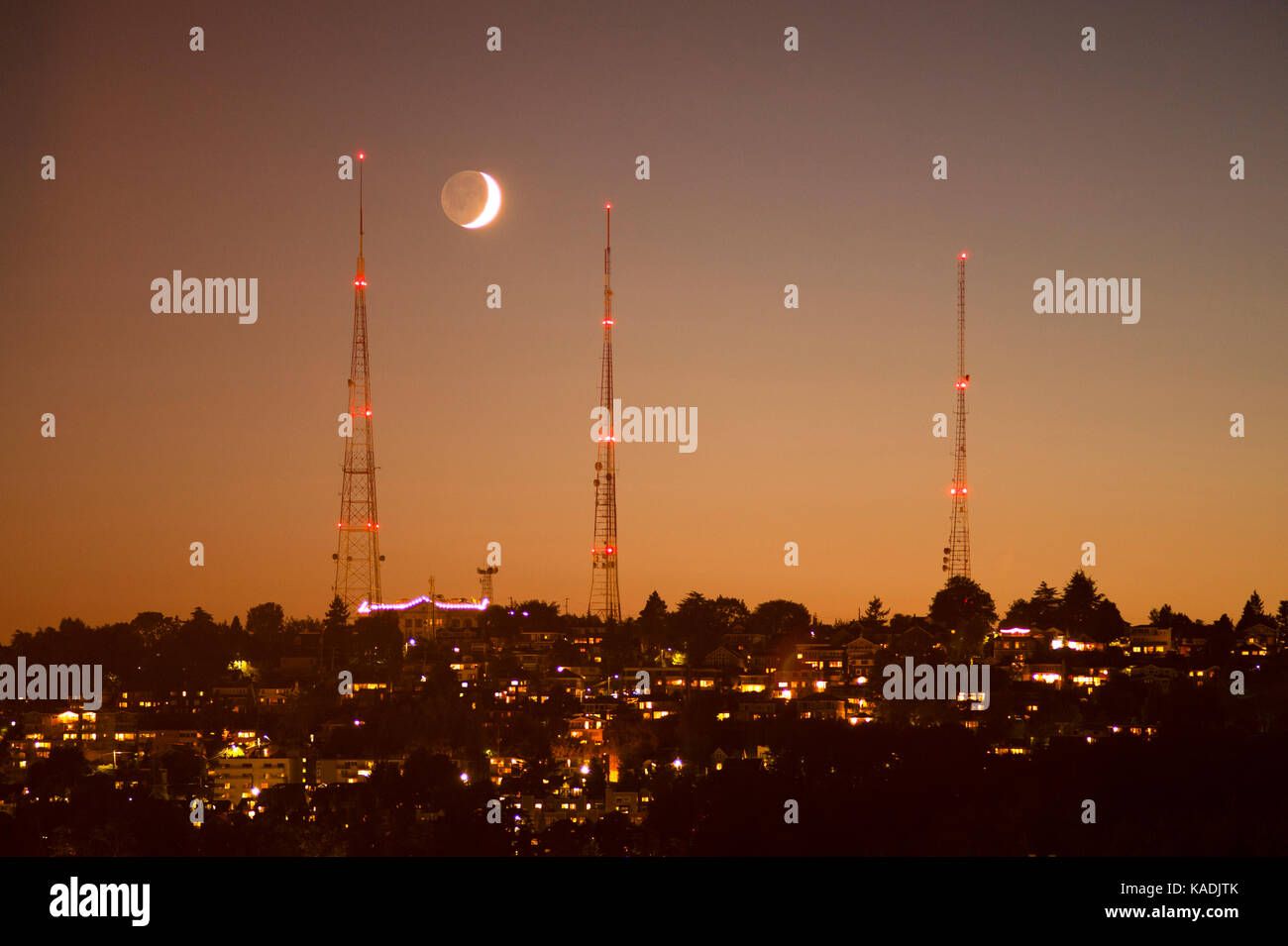 TV towers silhouetted at sunset with crescent moon setting over Queen Anne Hill - Stock Image