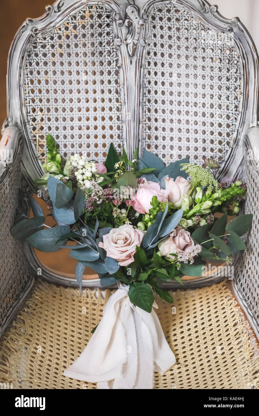 Bridal bouquet on vintage white wooden cane-chair Stock Photo