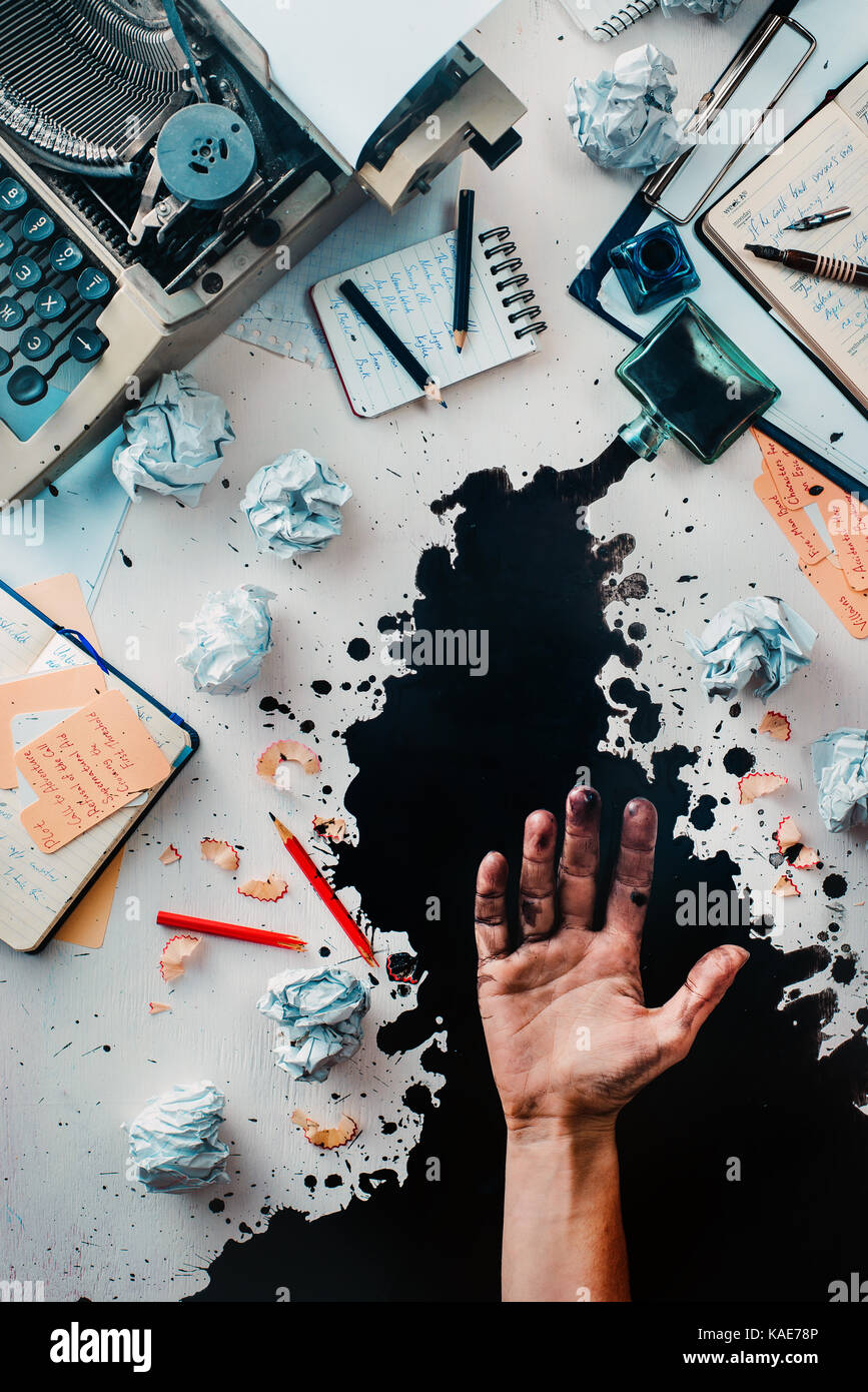 Writer workplace with spilled ink, crumpled paper, scattered letters, stationery and a typewriter. Ink leaving stains - Stock Image