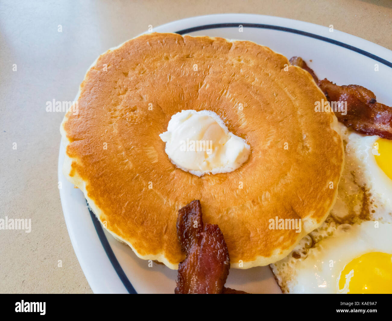 Close up shoot of traidional american breakfast of pancake with eggs and bacon, photo taken at a chain restaurant, - Stock Image