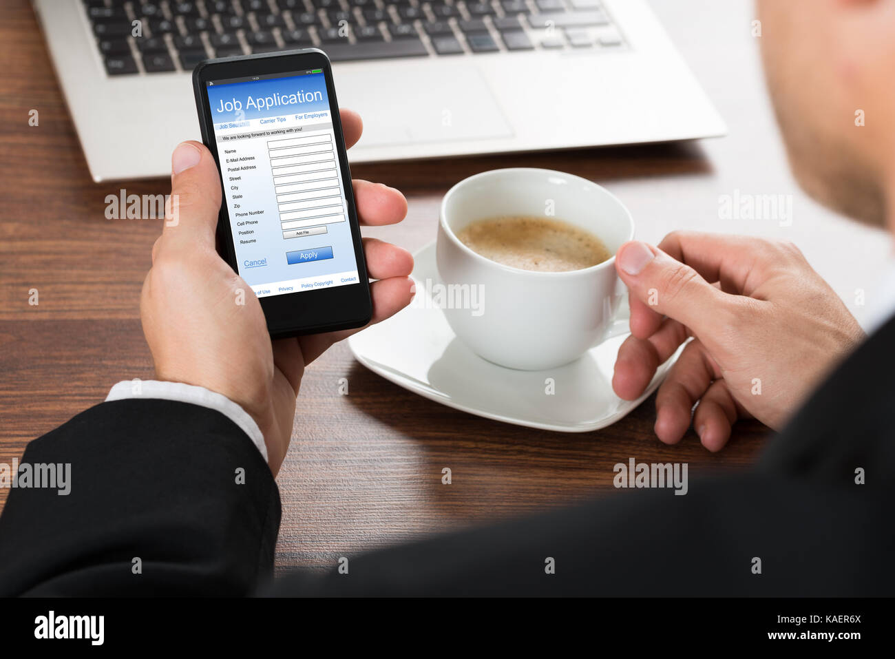 Close-up Of A Businessman Looking At Job Application Form On Cellphone While Having Coffee Stock Photo