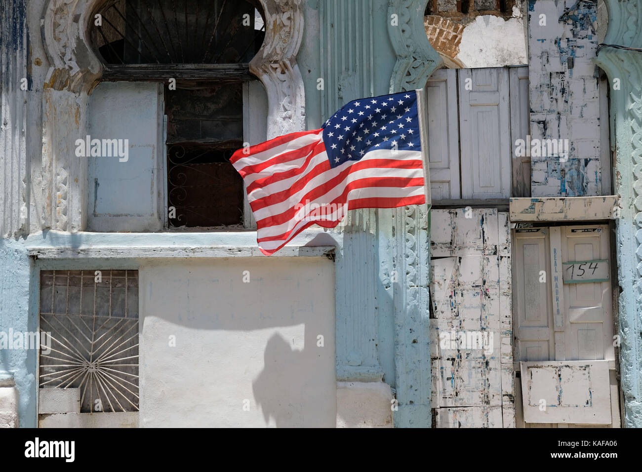 A United States flag flies outside a decrepit building in Centro Habana in Havana, Cuba. - Stock Image
