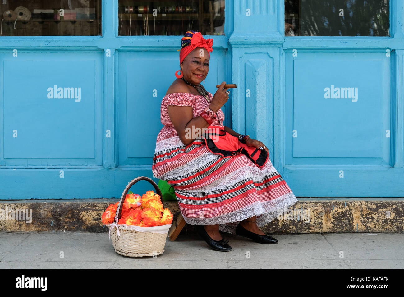A colourfully dressed Cuban woman in traditional clothing sits on the streets of Habana Vieja in Havana, Cuba. Stock Photo