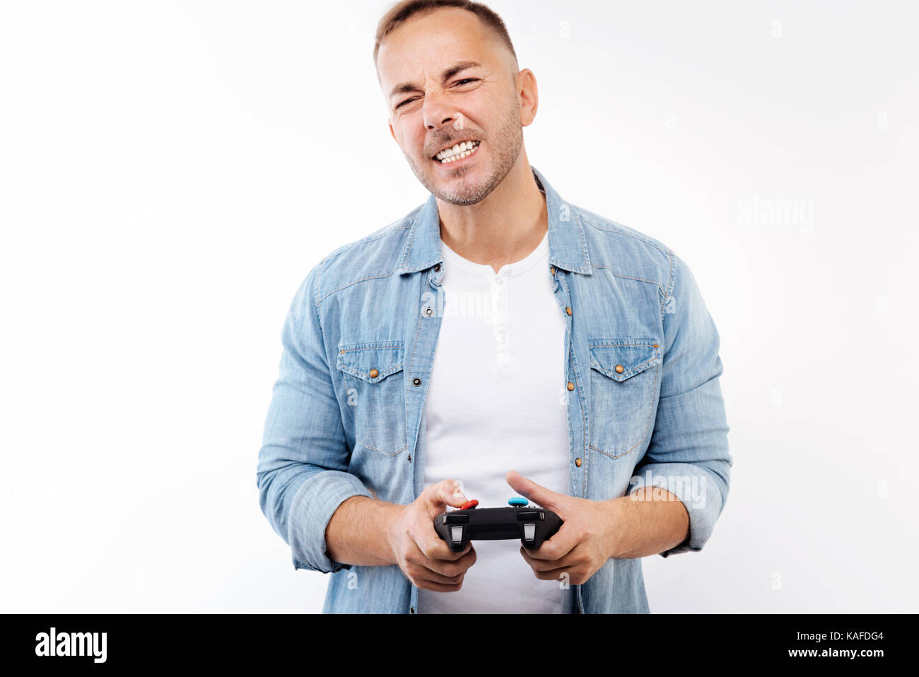 Young man grimacing after losing in video game - Stock Image