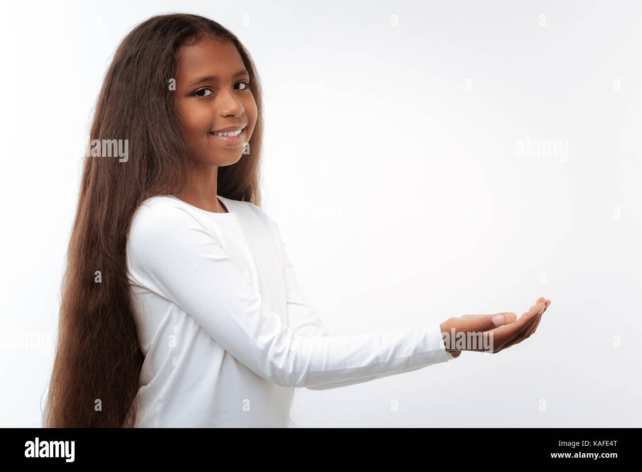 Smiling pre-teen girl cupping her hands in front of her - Stock Image