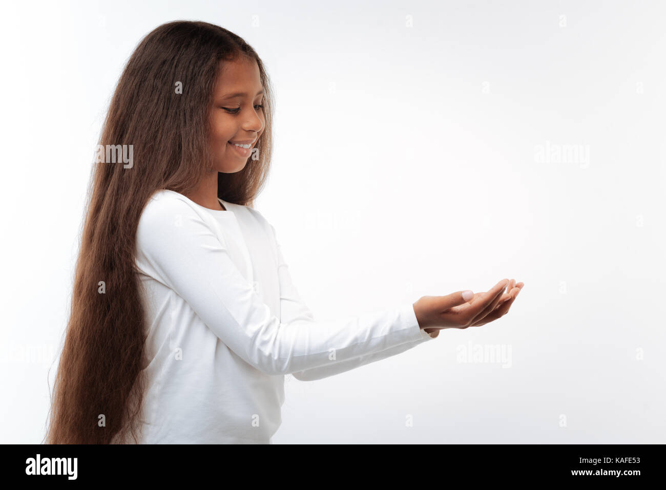 Beautiful pre-teen girl holding something small in her hands - Stock Image