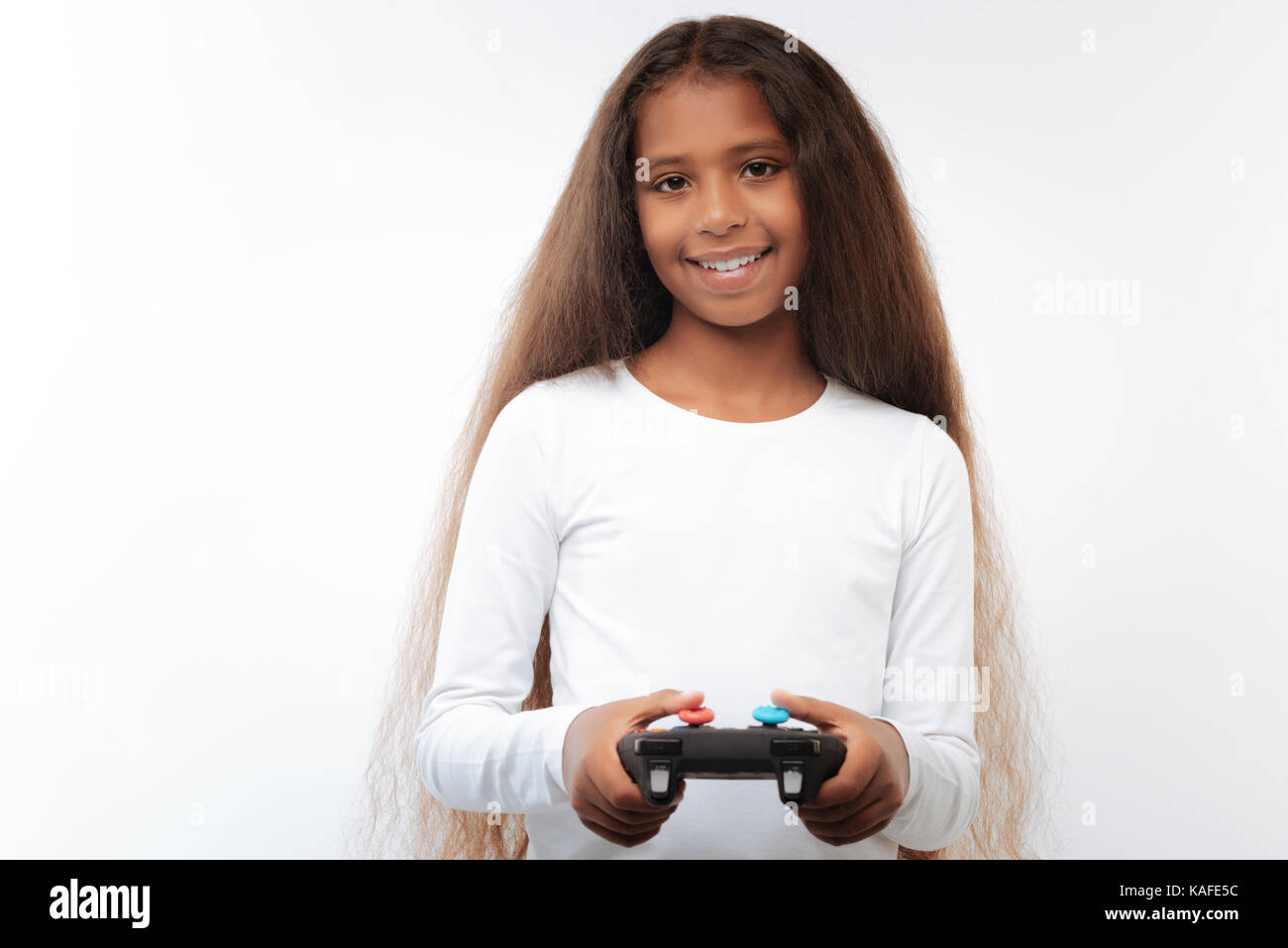 Pleasant pre-teen girl holding video game controller - Stock Image