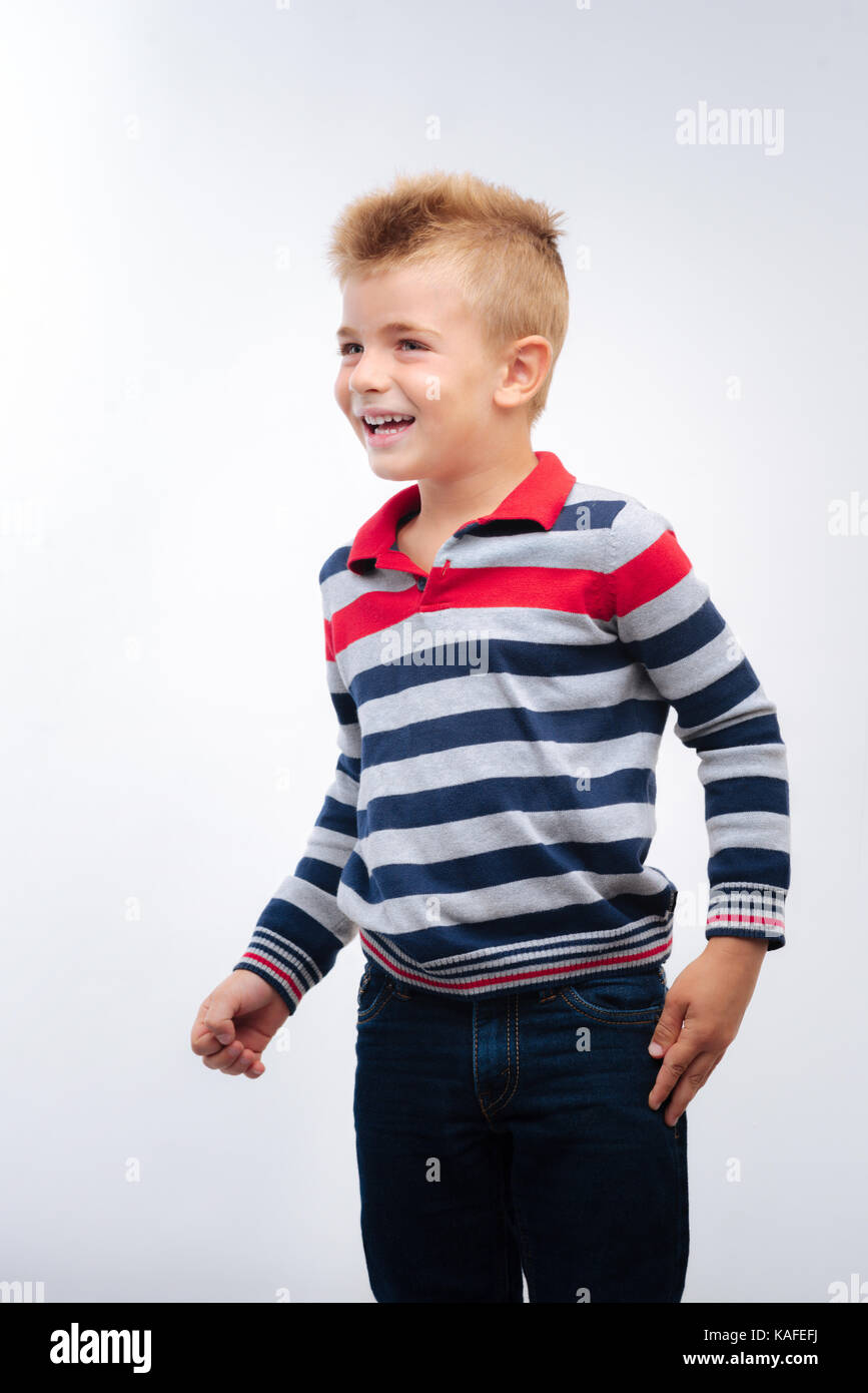 Lively little boy posing on white background - Stock Image