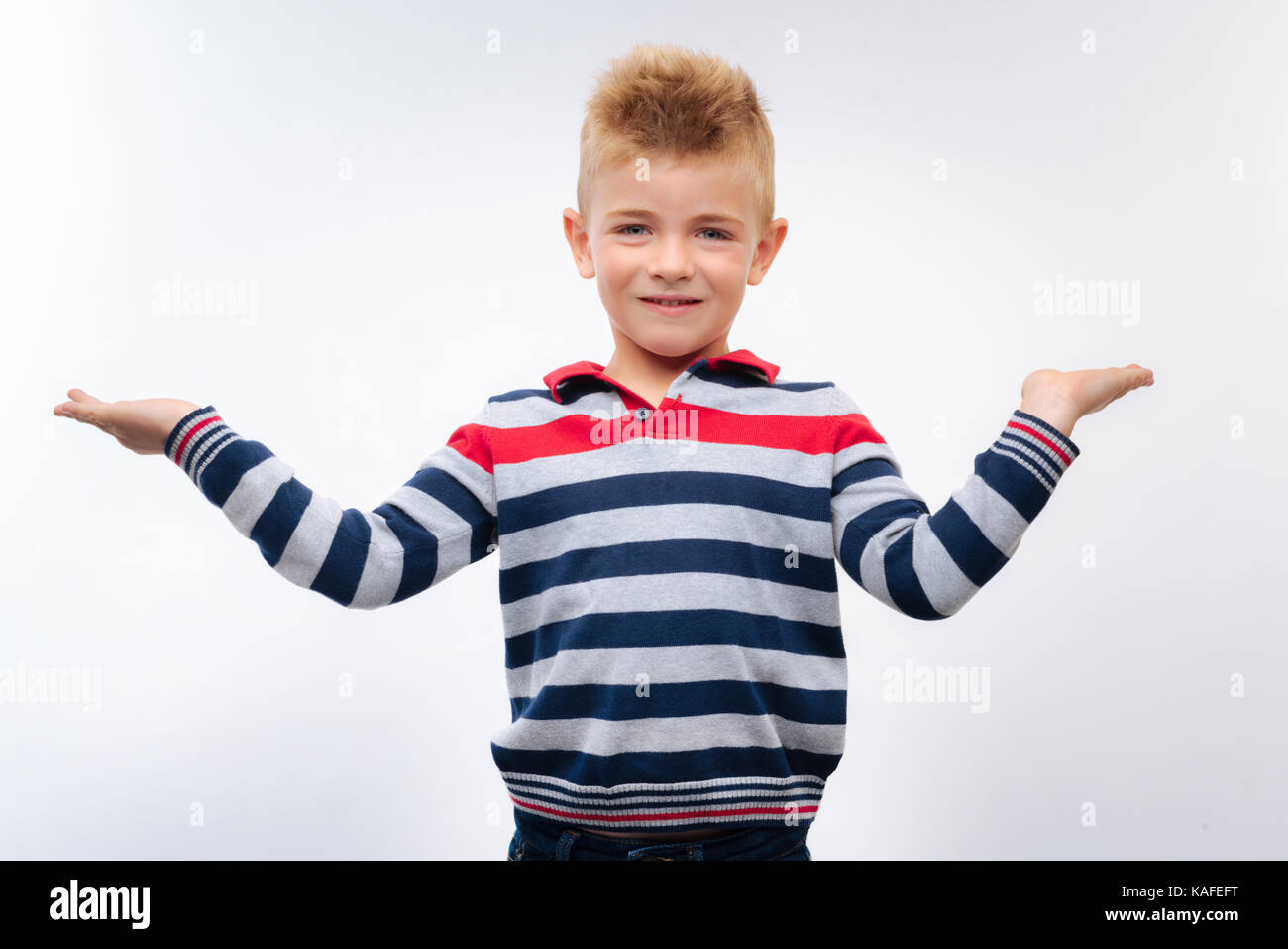 Smiling fair-haired boy spreading hands - Stock Image