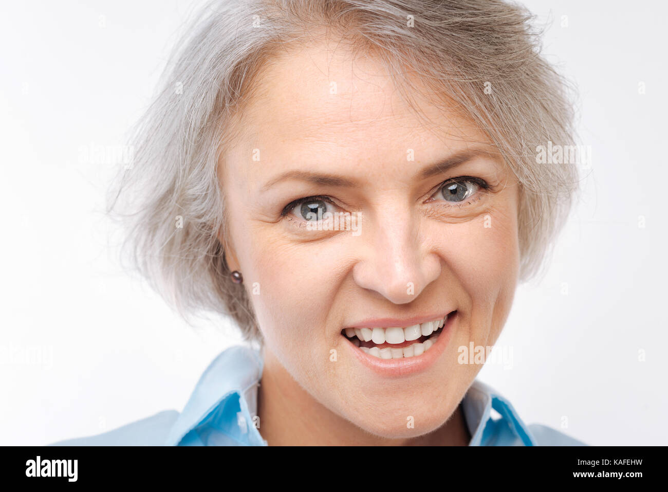Close up of grey-haired woman grinning at camera - Stock Image