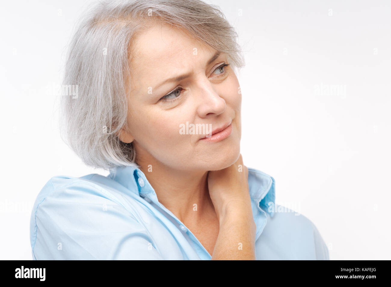 Close up of grey-haired woman suffering from neck pain - Stock Image