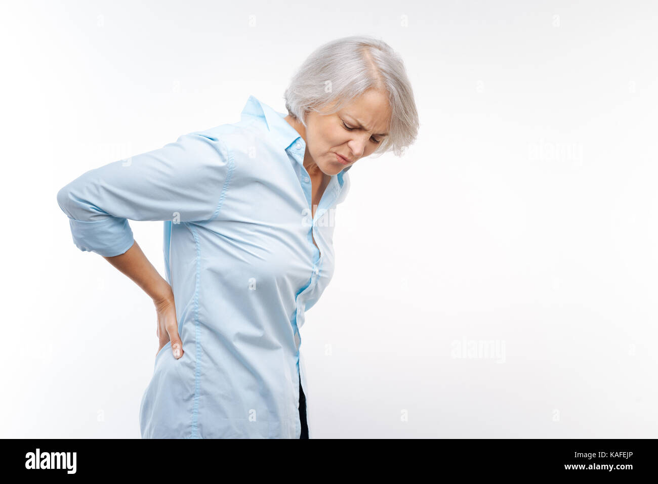 Grey-haired woman suffering from pain in lower back - Stock Image