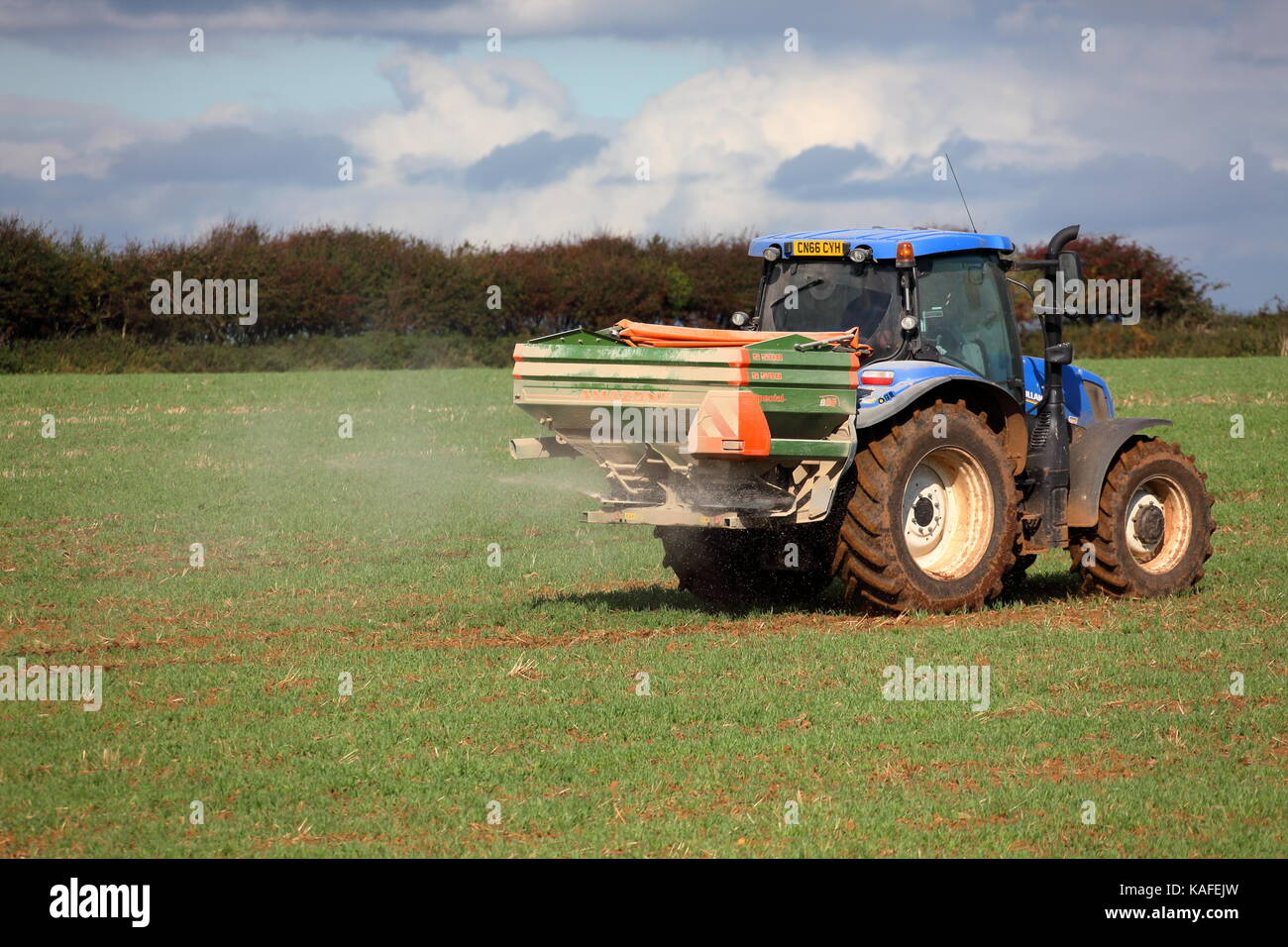 A farmer spreading fertiliser over a recently ploughed field with a tractor attached machine using spinning discs - Stock Image