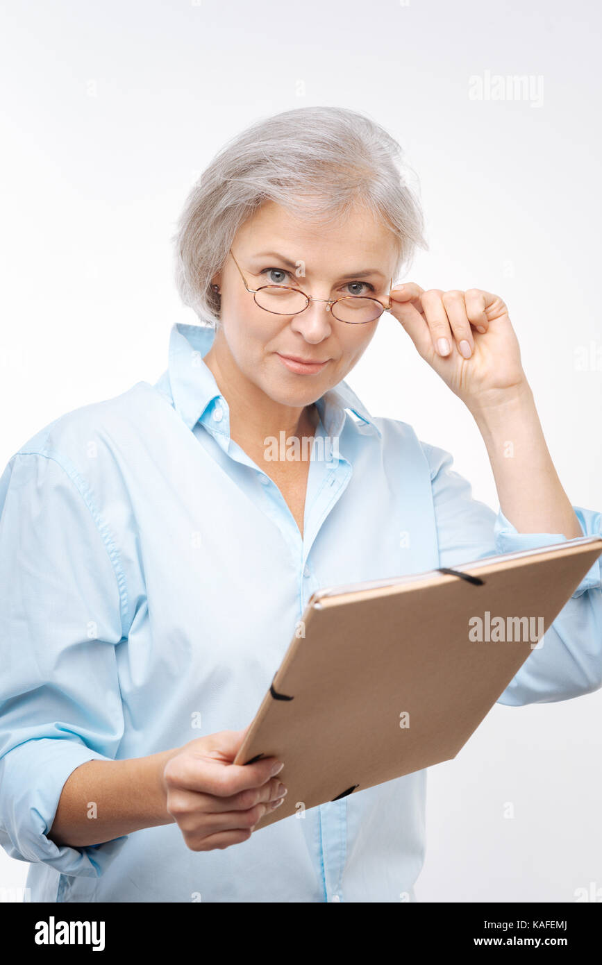 Pleasant woman with folder looking at camera - Stock Image