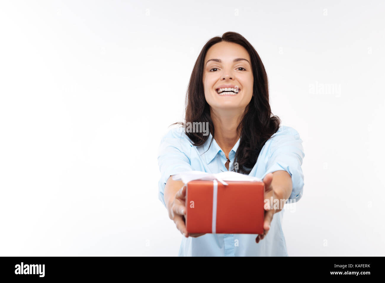 Happy young woman handing a red gift box - Stock Image
