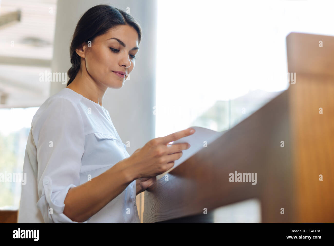 Delicate young woman reading at the cafe counter - Stock Image