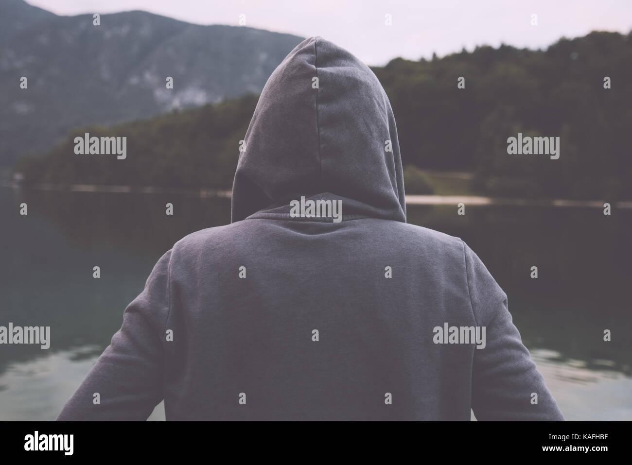 Gloomy nostalgic portrait of sad lonely melancholic adult female with hooded jacket standing on the lake shore in - Stock Image